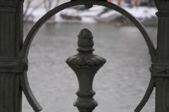 An iron fence frames the cold waters of the River Vltava