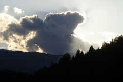 The sun behind the clouds over Triglav